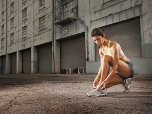 A woman runner leaning down and tying her running shoes laces.の写真素材 [FYI02251344]