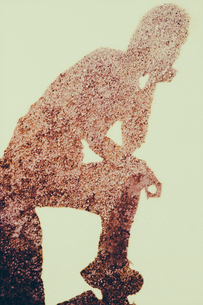The outline of a human body, a shadow against a plain background in a pensive pose.の写真素材 [FYI02251348]