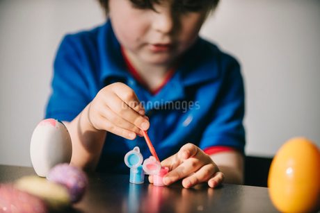 A boy sitting at a table decorating painting eggs.の写真素材 [FYI02251349]