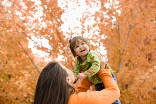 A woman holding a small child up in the air, under a canopy of autumn foliage.の写真素材 [FYI02251350]