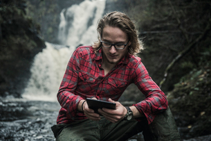 A man sitting by a fast flowing stream using a digital tablet.の写真素材 [FYI02251352]