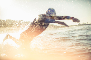 A swimmer in a wet suit running into the water, making a splash.の写真素材 [FYI02251353]