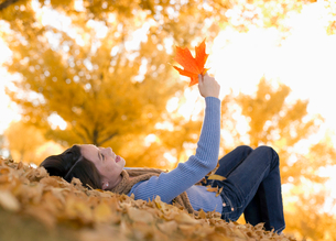 A girl holding up a large orange autumn coloured maple leaf.の写真素材 [FYI02251376]