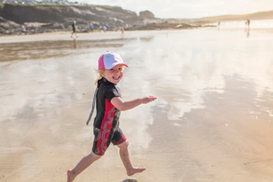 A child in a wetsuit running on sandの写真素材 [FYI02251377]