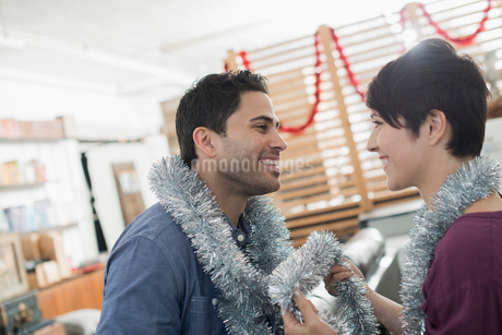 A room decorated with tinsel and streamers. A man and woman wearing silver tinsel around their necksの写真素材 [FYI02251379]