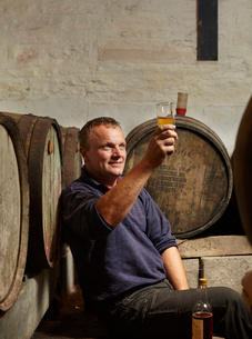 A man sitting among oak barrels at a cider makers, raising a glass and tasting the brew.の写真素材 [FYI02251395]