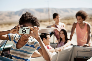 A group of friends by a pale blue convertible on the open road, on a flat plain surrounded by mountaの写真素材 [FYI02251397]