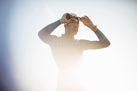 A swimmer in a wetsuit and swimming hat, adjusting his swimming goggles.の写真素材 [FYI02251400]