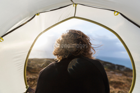 A man sitting in the shelter of a tent looking out.の写真素材 [FYI02251401]
