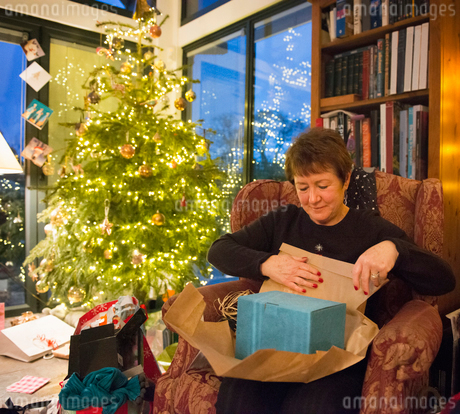 A mature woman in an armchair unwrapping her presents beside a Christmas tree.の写真素材 [FYI02251414]