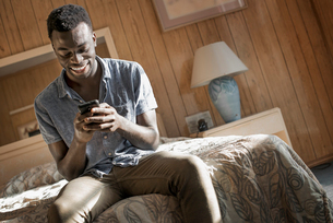 A young man in a motel room checking his smart phone.の写真素材 [FYI02251417]