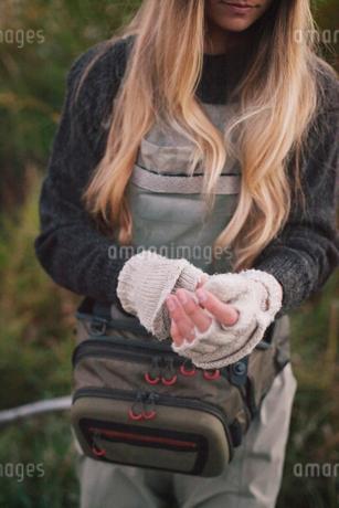 A woman with long blonde hair putting on woollen fingerless mittens.の写真素材 [FYI02251426]