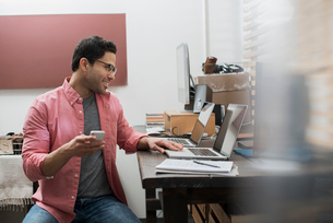 A man in a home office with a desk with two laptops, checking information on the screen, holding a sの写真素材 [FYI02251430]
