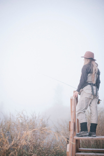 A woman standing on a wooden style in mist.の写真素材 [FYI02251444]