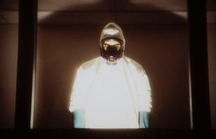 A man wearing a hazardous material protective clean suit, a hazmat suit, standing behind windowの写真素材 [FYI02251451]