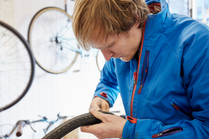 A young man working in a cycle shop, repairing a bicycle.の写真素材 [FYI02251456]