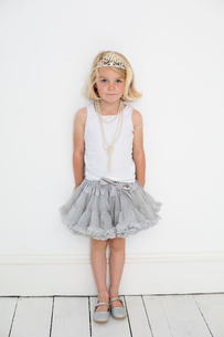 Young girl wearing a tiara and a pearl necklace, posing for a picture in a photographers studio.の写真素材 [FYI02251463]