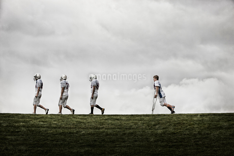A group of football players, young people in sports uniform and protective helmets. Three fit playerの写真素材 [FYI02251467]