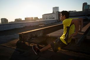 A man in exercise clothes on a rooftop overlooking the city, doing bench shoulder push ups.の写真素材 [FYI02251471]