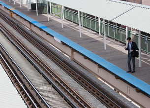A working day. A view down on a railway station and a man waiting on the platform.の写真素材 [FYI02251477]