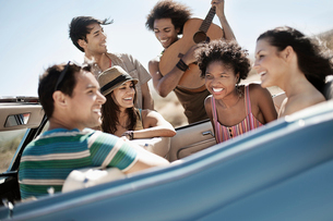 A group of friends in a pale blue convertible on the open road, driving across a dry flat plain surrの写真素材 [FYI02251478]