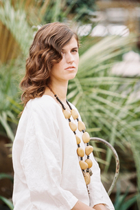 A young woman with curly brown hair wearing white shirt and necklace.の写真素材 [FYI02251485]