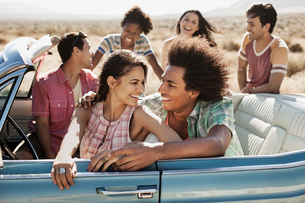 A group of friends in a pale blue convertible on the open road, driving across a dry flat plain surrの写真素材 [FYI02251497]