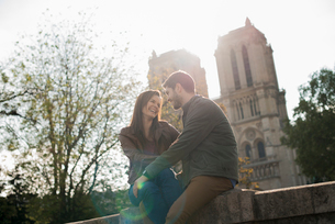 A couple in a romantic mood, side by side with arms around each other outside Notre Dame Cathedral iの写真素材 [FYI02251526]