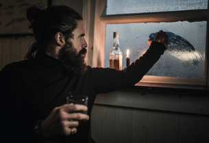 A man sitting alone in a room with a bottle of whisky and a glass, wiping condensation off the windoの写真素材 [FYI02251529]