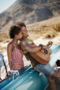 A young couple standing by a pale blue convertible on the open road, the man playing a guitar.の写真素材 [FYI02251545]