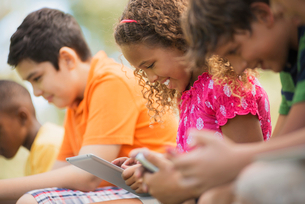 A row of children sitting outdoors in summer using tablets and handheld games.の写真素材 [FYI02251557]