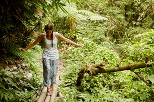 A woman walking carefully across a bamboo bridge in the jungle.の写真素材 [FYI02251559]