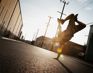 A young man breakdancing on the street of a city, doing a one handed handstand.の写真素材 [FYI02251566]