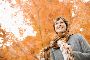 A woman in a jacket and neck scarf against a backdrop of autumn trees in vivid colour.の写真素材 [FYI02251571]