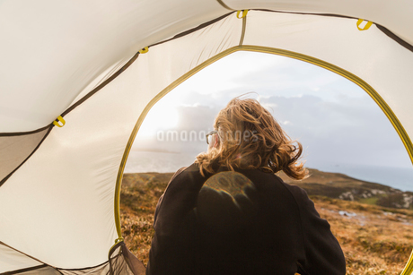 A man sitting in the shelter of a tent looking out.の写真素材 [FYI02251577]