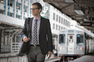 A working day. Businessman in a work suit and tie on a railway station platform.の写真素材 [FYI02251580]