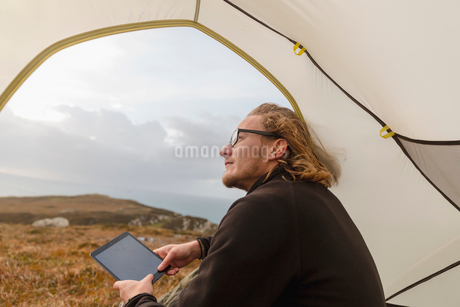 A man sitting in the shelter of a tent looking out, holding a digital tablet.の写真素材 [FYI02251587]