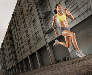 A woman running along an urban road, legs high and arms pumping.の写真素材 [FYI02251589]