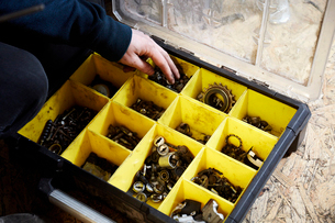 A man working in a cycle shop, reaching for parts in a box of spares.の写真素材 [FYI02251598]