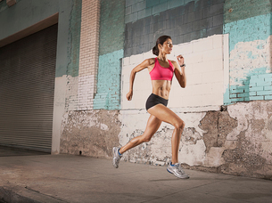 A woman running along an urban street past buildings with peeling paint and a metal shutter.の写真素材 [FYI02251602]