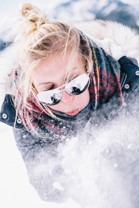 A young woman in sunglasses blowing fresh snow off her hands.の写真素材 [FYI02251616]