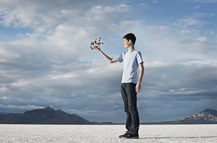 A teenage boy holding a molecular structure in his hands.の写真素材 [FYI02251617]