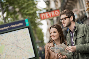 A couple using a street map beside an information sign under a metro sign in a city.の写真素材 [FYI02251630]