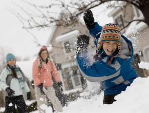 Winter snow. Three children having a snowball fight.の写真素材 [FYI02251644]
