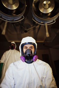 Two men wearing protective clean suits in a hospital room with lights on the ceiling.の写真素材 [FYI02251649]