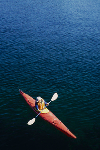A man in a sea kayak on the calm waters off the coast of Southeast Alaska.の写真素材 [FYI02251650]