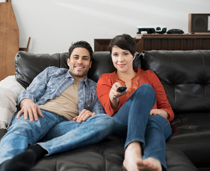 A man and woman sitting on a sofa, side by side, one using the remote control for the tv.の写真素材 [FYI02251658]