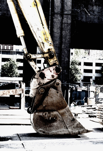 Backhoe shovel at a building site, resting on the ground.の写真素材 [FYI02251659]