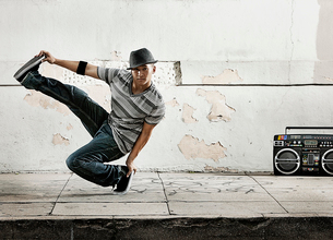 A young man breakdancing, balancing on one foot with his leg outstretched.の写真素材 [FYI02251661]