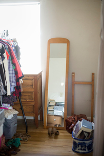 Mirror, chest of drawers, clothes rack and shoes in a bedroom.の写真素材 [FYI02251662]